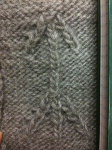 A swatch of knitted fabric showing a cabled arrow pointing upwards.